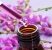 closeup of a dropper bottle and a pile of purple flowers on a pu