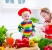 Two little children adorable toddler girl in red chef hat and apron and funny baby boy preparing healthy lunch making delicious salad with fresh vegetables and garden herbs in a white sunny kitchen